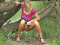 Playful girl pulls down her panties and takes a leak on the river bank
